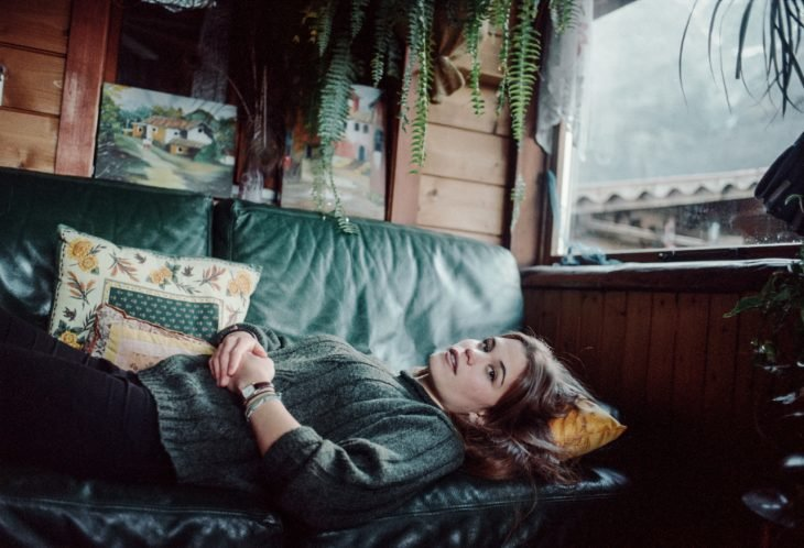 chica recostada en sillón en una cabaña