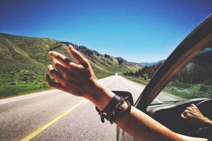 mano de chica por ventana de coche en carretera