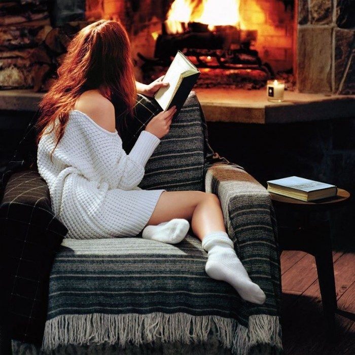 chica sentada en silla leyendo frente a chimenea