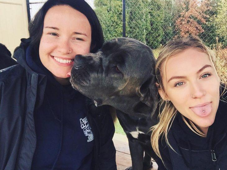 dos amigas con un perro negro en medio
