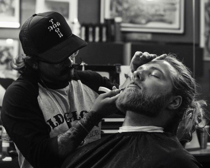 hombre rubio sentado mientras le cortan barba