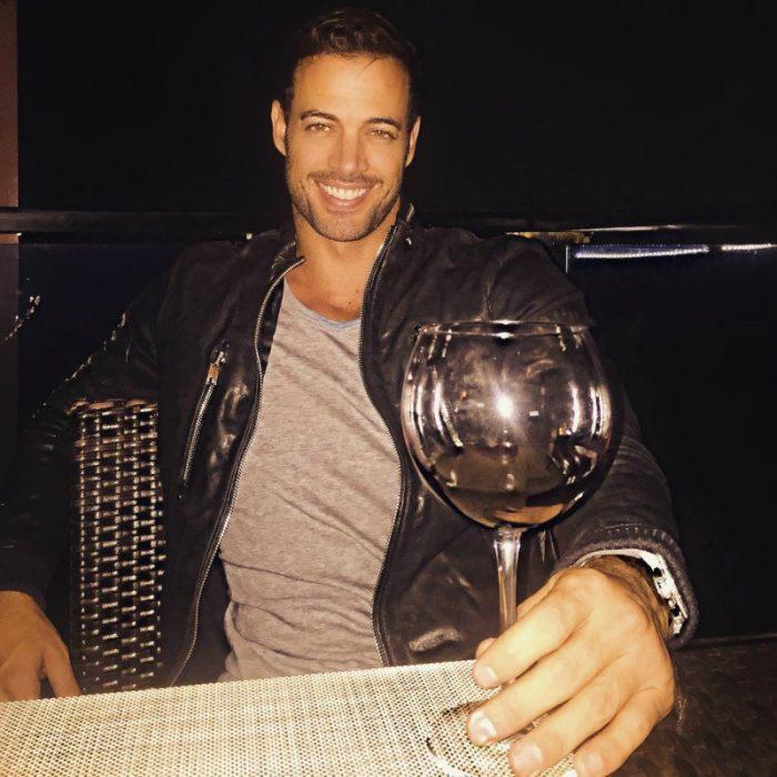 hombre sentado en una mesa con una copa de vino