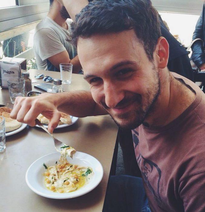 hombre sentado sonriendo comiendo hummus