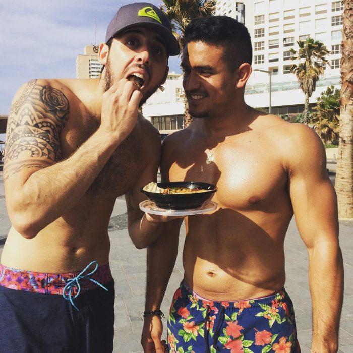 hombres en la playa sin playera comiendo