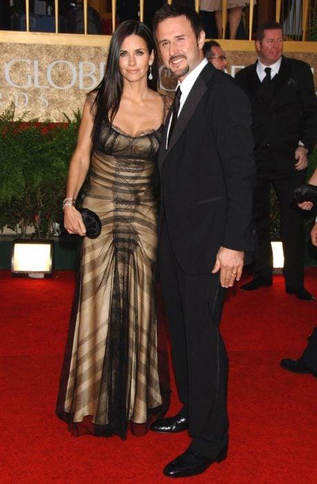 mujer cabello negro con vestido y hombre castaño de traje