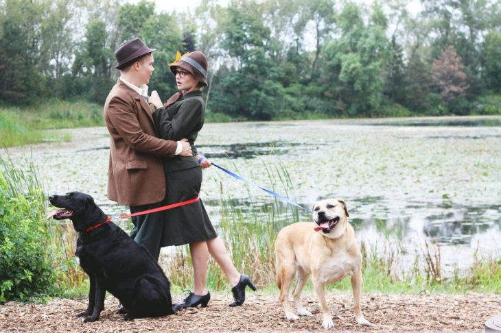 pareja se cruza y dos perros con correa