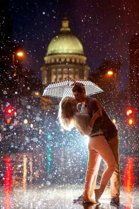 pareja dandose un beso bajo la lluvia y sombrilla