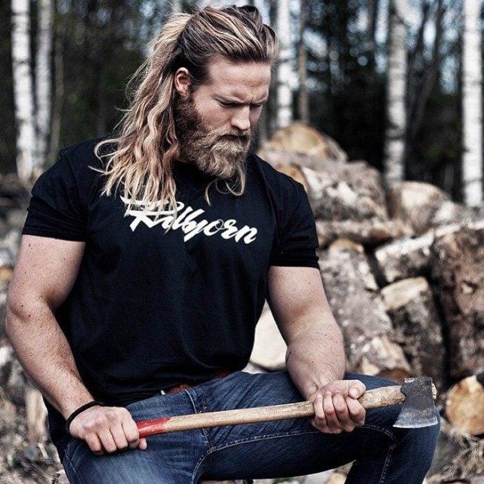 hombre rubio con hacha y troncos