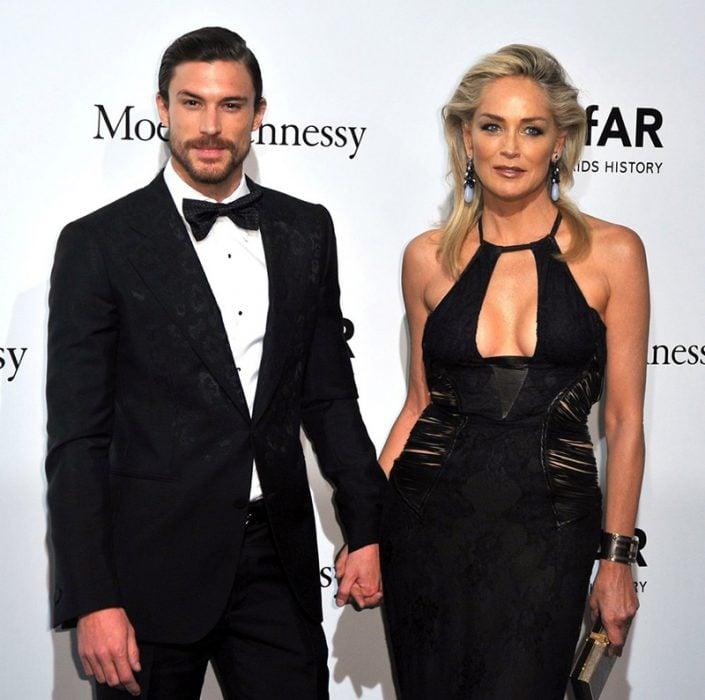 hombre con traje tomado de la mano y mujer rubia de vestido negro