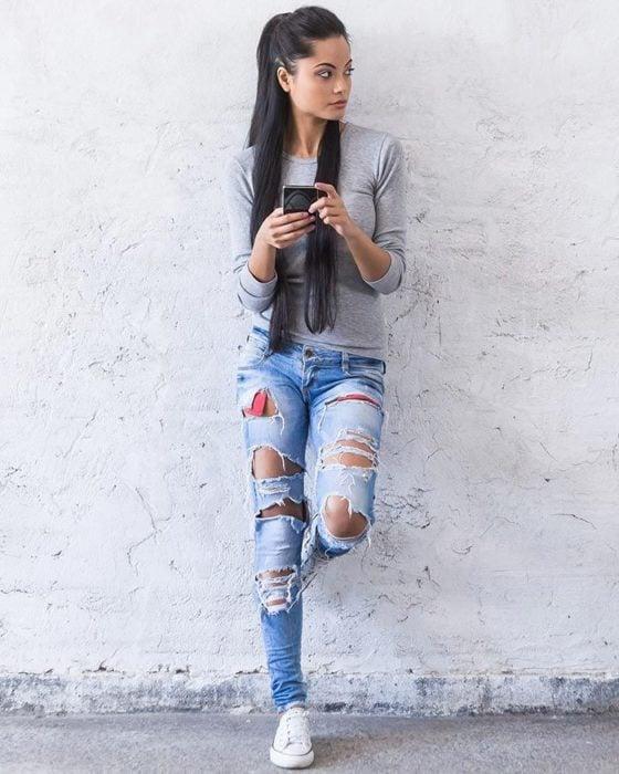 Chica recargada en una pared llevando jeans rotos
