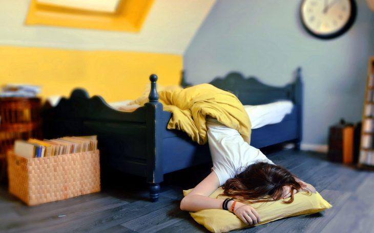 Chica durmiendo con medio cuerpo fuera de la cama