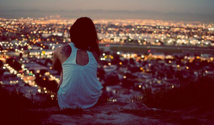 chica sentada en una colina observando la ciudad