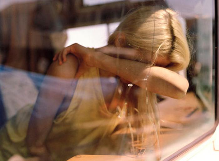 chica en ventana del coche cubriendo su cara