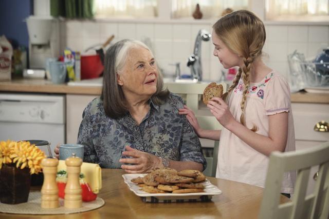 abuela y nieta comiendo galletas en la cocina