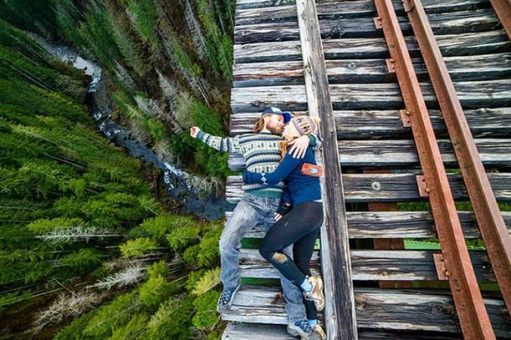 pareja acostada en la orilla de un puente