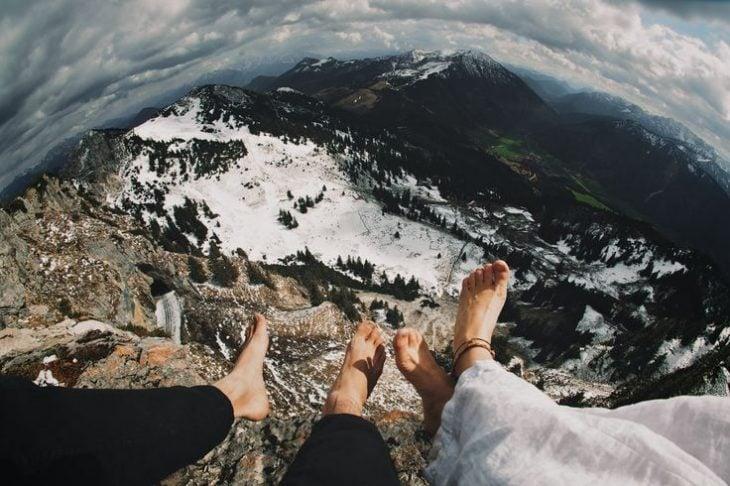 pies de pareja en la cima de una montaña