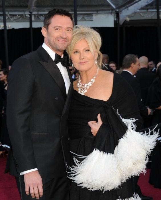 hombre saco y moño y mujer de vestido negro