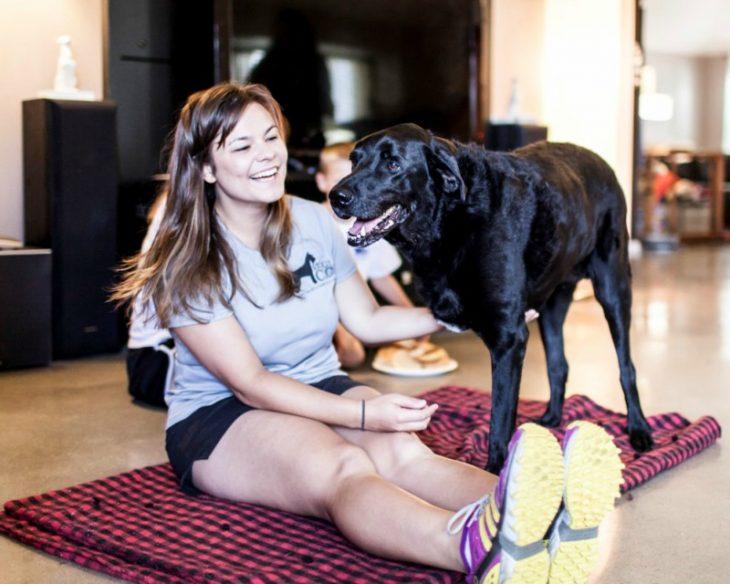 mujer sonriendo con un perro con 3 patas