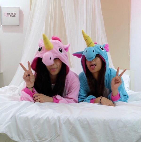 Chicas recostadas sobre una cama vestidas como unicornios
