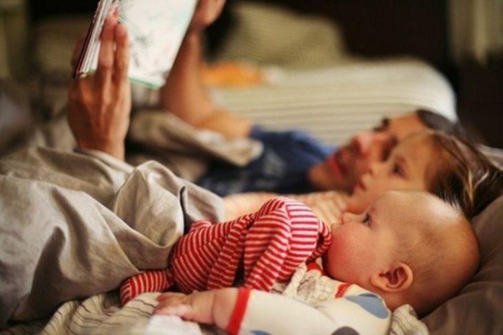 padre leyendo cuentos a hijos pequeños