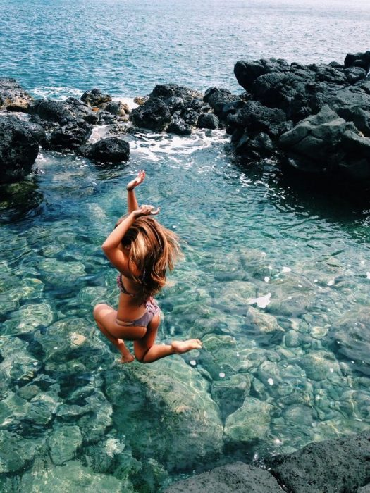 chica aventándose desde lo alto al agua