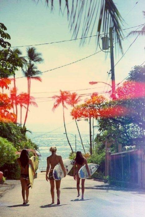 chicas con tabla de surf caminando