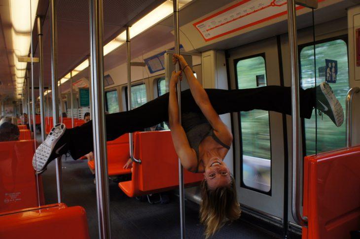 chica colgada de un tubo en vagón de metro
