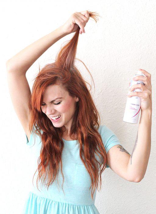 chica rociándose spray en cabello