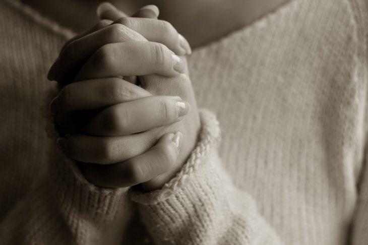 mujer con manos en posición de oración