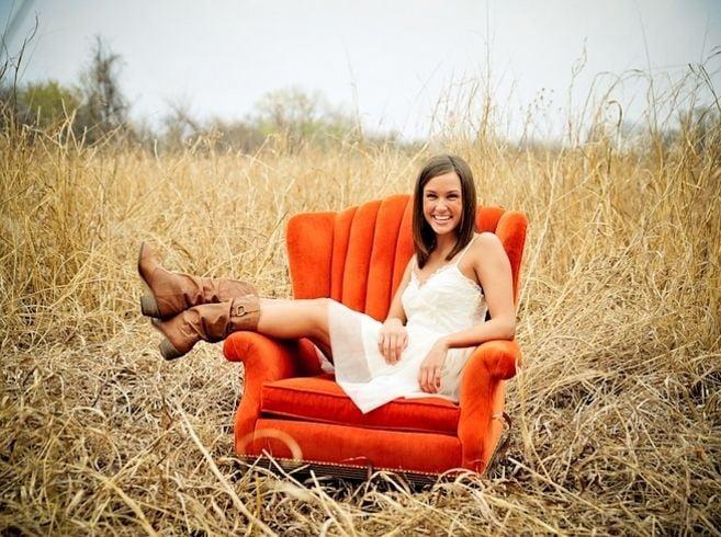 chica sentada en sillón naranja en el pastizal