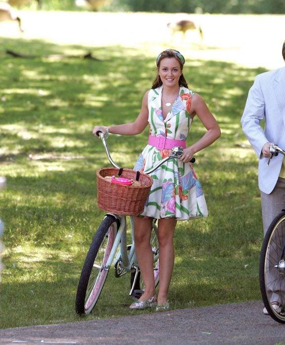 Blair Waldorf usando un vestido floreado con un cinturón rosa mientras sujeta una bicicleta