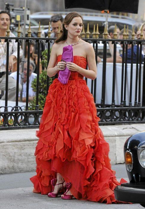 Blair Waldorf usando un vestido en color naranja con un bolso y zapatos en color rosa