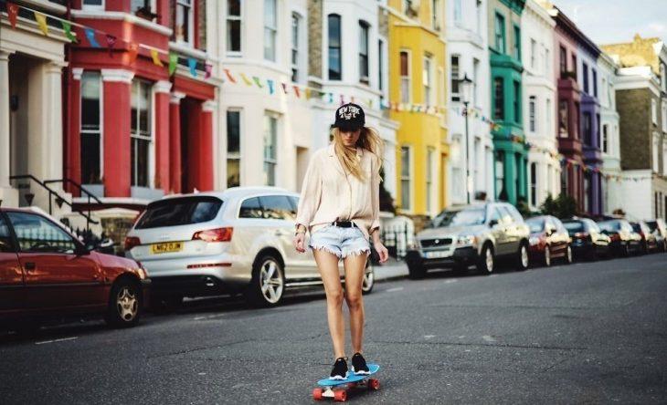 chica en patineta en la calle mirando hacia abajo