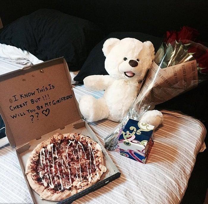 pizza con oso y flores en una cama