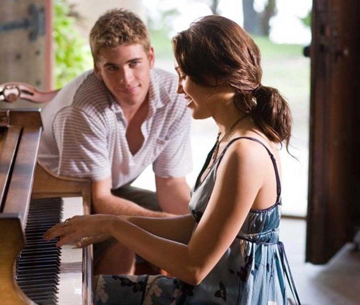 hombre mira a su novia tocar el piano