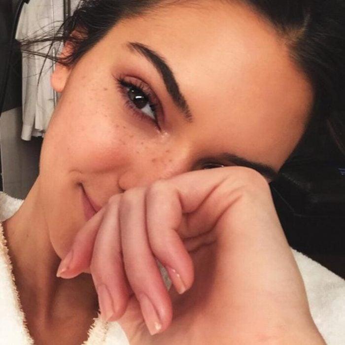 mujer sin maquillaje con mano en la cara sonriendo