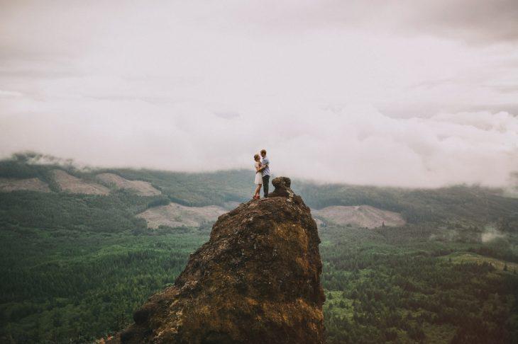 pareja de pie en una montaña con paisaje alrededor