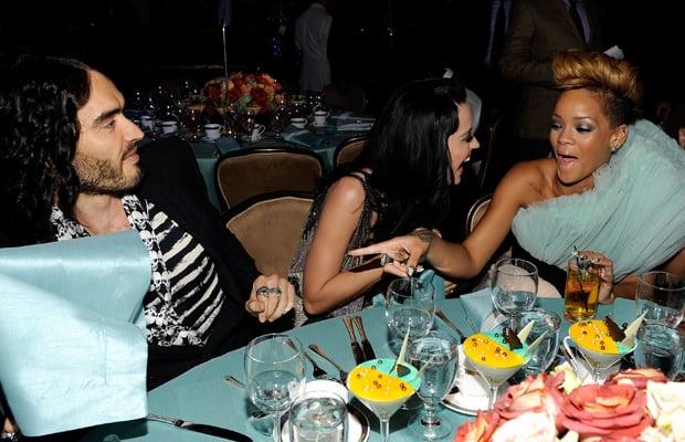mujeres sentadas en una mesa riendose y apuntan a hombre