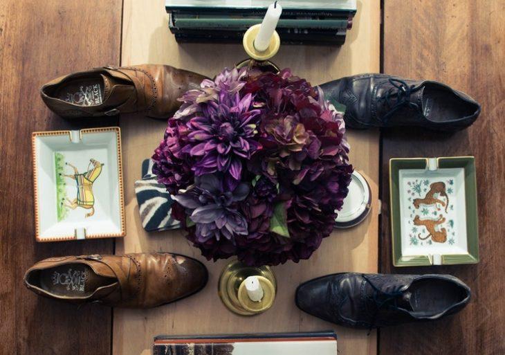 flores en la mesa con zapatos de hombre
