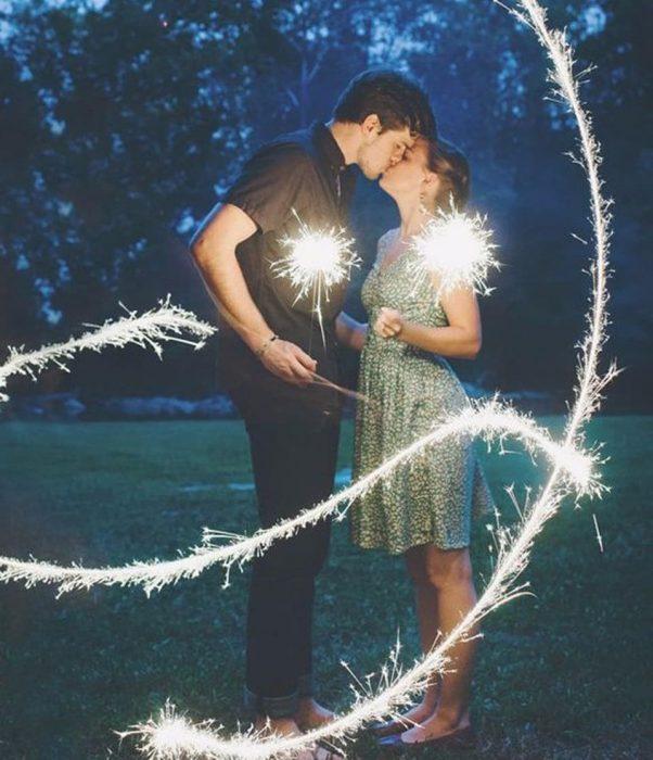 Pareja de pie se dan besos con luces de bengala