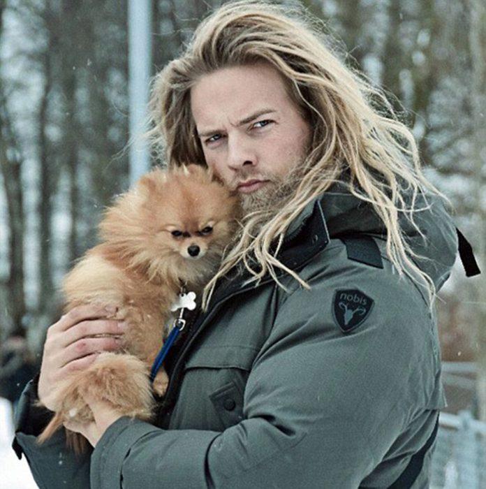 hombre rubio cabello largo, barba y perro