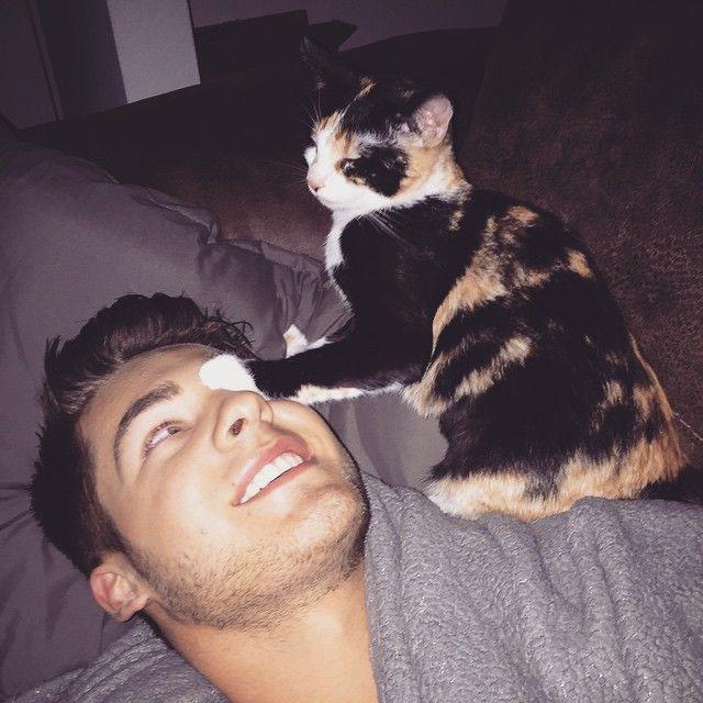 hombre acostado sonrie jugando con un gato