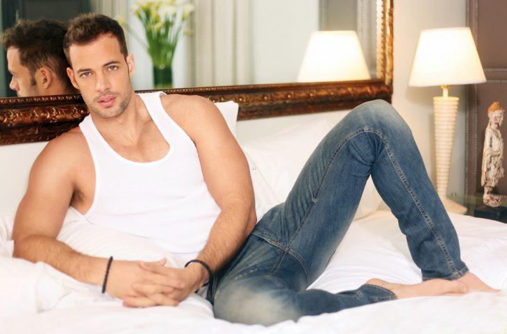 Hombre con camisa blanca acostado en la cama