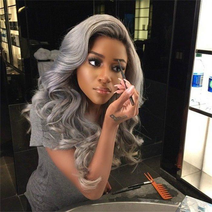 mujer morena maquillandose frente al espejo con cabello color gris