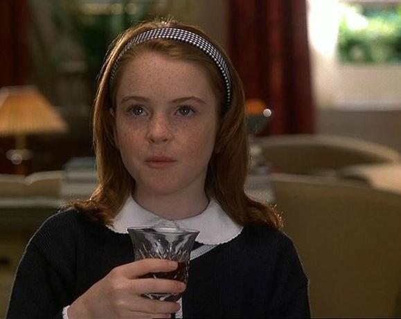 niña sentada tomando una copa de vino