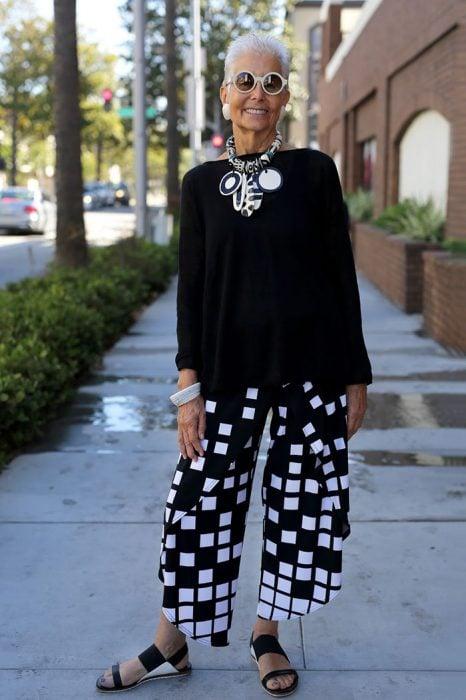 Mujer mayor usando un traje negro con cuadros blancos y negros