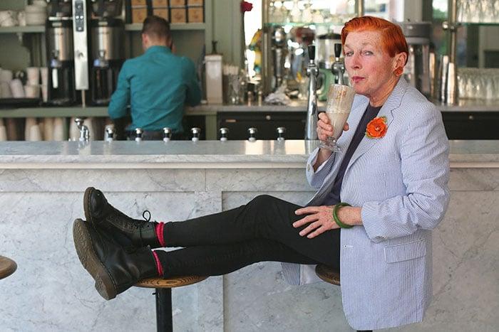 Mujer mayor con un saco en color gris pantalones negros tomando una malteada en un restaurante