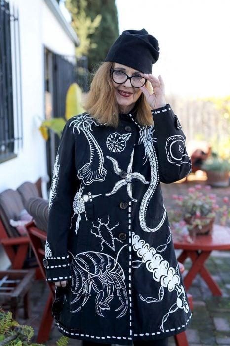 Mujer mayor usando una chaqueta en color negro y gorro