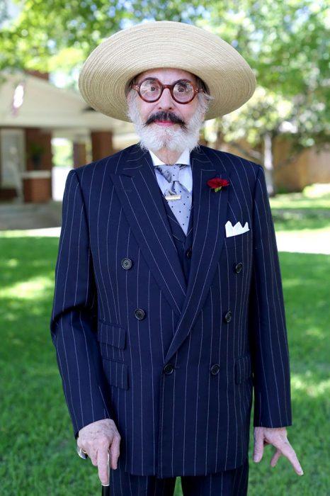 Hombre mayor usando un traje en color azul con rayas blancas y un sombrero de paja