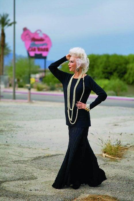 Mujer mayor usando un vestido en color negro con collares en color perla